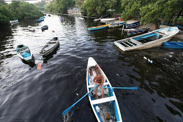 RIO DE JANEIRO, BRAZIL - JANUARY 21: A man boats on an inlet of the polluted waters of Guanabara Bay in the Ilha do Governador neighborhood on January 21, 2014 in Rio de Janeiro, Brazil. The iconic bay will be the site of sailing events during the Rio 2016 Olympic Games. Although Rio's Olympic bid included the promise to clean up the filthy bay, industrial and human pollution still remain a major problem. According to the Deputy State Secretary of Environment just 34% of Rio's sewage is treated while the remainder flows untreated into the waters. (Photo by Mario Tama/Getty Images)