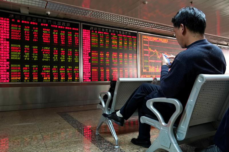 An investor uses his mobile phone in front of a stock quotation board at a brokerage office in Beijing, China January 3, 2020. REUTERS/Jason Lee