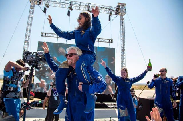 Virgin Galactic founder Sir Richard Branson carries crew member Sirisha Bandla on his shoulders while celebrating their flight to space at Spaceport America in New Mexico