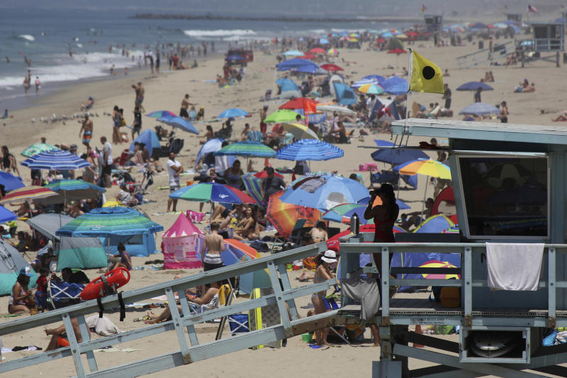 FILE - In this July 8, 2017 file photo a lifeguard scans a crowded shoreline at Manhattan Beach, Calif. California's population has stalled at 39 million people. An estimate released Friday, Dec. 20, 2019, showed the state had 39.96 million people as of July 1. (AP Photo/John Antczak,File)
