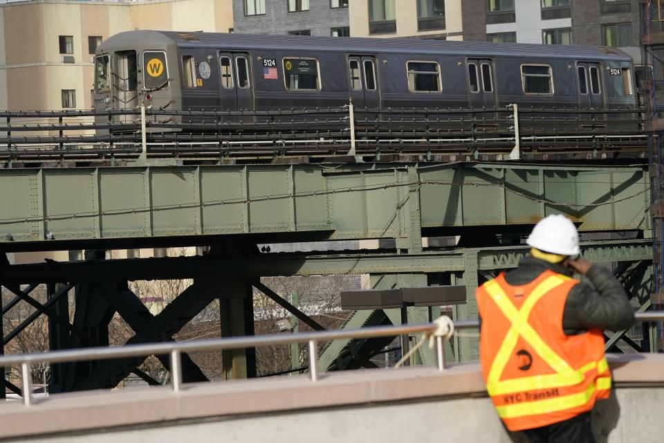The W train passes an MTA official at the Mid-Day Storage Yard Services Building during a news conference on Positive Train Control, a federally mandated rail safety technology, Wednesday, Dec. 23, 2020, in the Queens borough of New York. (AP Photo/Frank Franklin II)