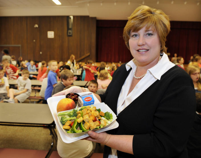 Food Service's Director Kim Gagnor, poses for a photograph with select healthy food items from the lunch line of the cafeteria at Draper Middle School in Rotterdam, N.Y., Tuesday, Sept. 11, 2012. The leaner, greener school lunches served under new federal standards are getting mixed grades from students. (AP Photo/Hans Pennink)