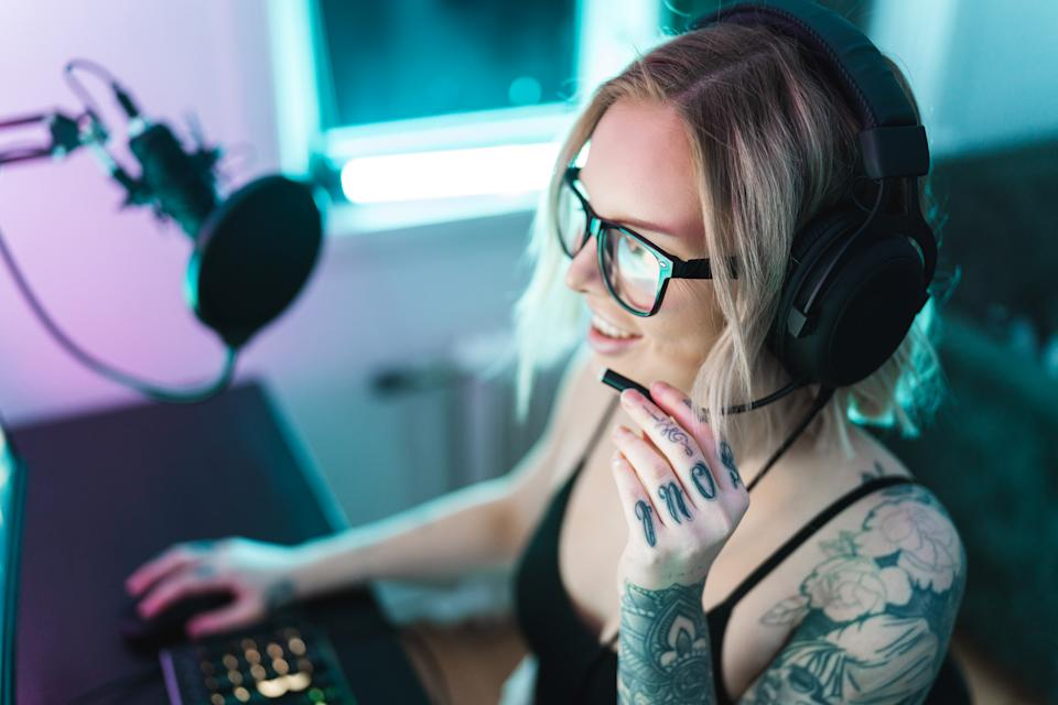 A female gamer and streamer is playing video games on her computer. She is talking to her online friends and followers.