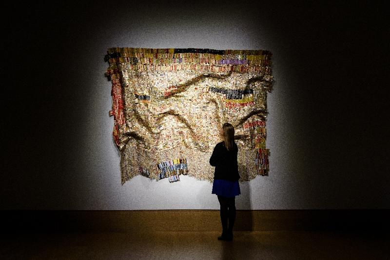 """A member of the auction house staff poses by """"Peju's Robe"""" by Ghanaian sculptor El Anatsui during a photocall on Febuary 1, 2016 to promote Bonham's upcoming """"Post-War and Contemporary Art"""" sale in London (AFP Photo/Leon Neal)"""