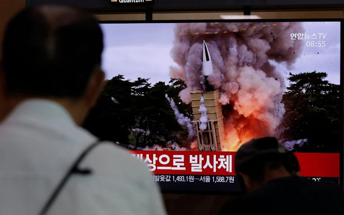 People watch a TV news programme reporting North Korea's firing projectiles at the Seoul Railway Station - AP