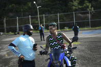 Motorcycle stuntman Pedro Aldana speaks with a police officer after officers stopped his previously authorized exhibition, citing COVID-19 restrictions, on Camuri Chico beach in La Guaira, Venezuela, Saturday, Jan. 30, 2021. Soldiers have also refused to let his crew of adrenaline junkies hold an exhibition in the streets of Caracas, where neighbors are starved for entertainment. (AP Photo/Matias Delacroix)