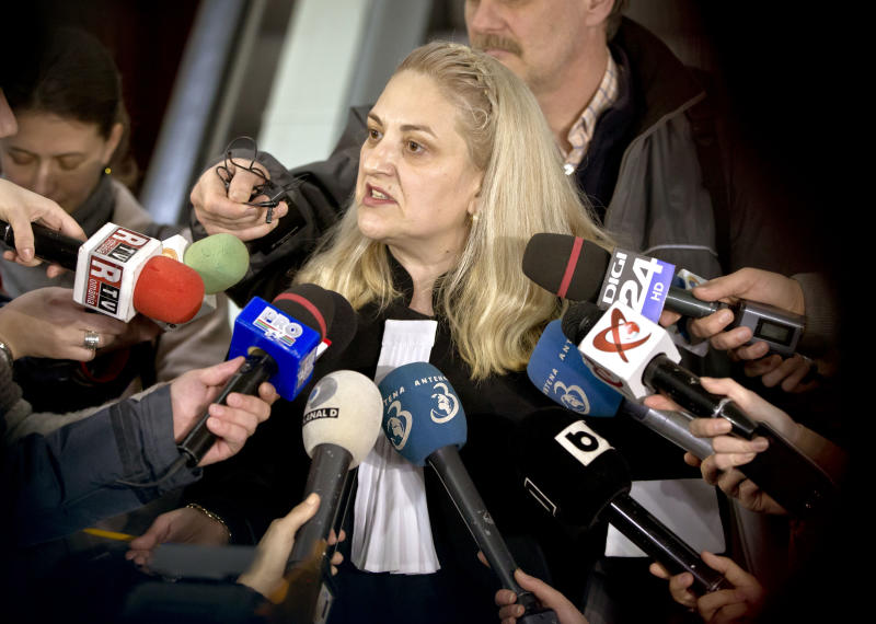 Doina Lupu, lawyer of Radu Dogaru and Eugen Darie, not seen, is surrounded by the media in Bucharest, Romania, Friday, Jan. 25, 2013. Lawyers for three Romanians Mihai Alexandru Bitu, Radu Dogaru and Eugen Darie, charged with stealing valuable paintings from a museum in the Netherlands last year, including works by Picasso, Monet and Matisse say there is insufficient evidence to charge them. (AP Photo/Vadim Ghirda)