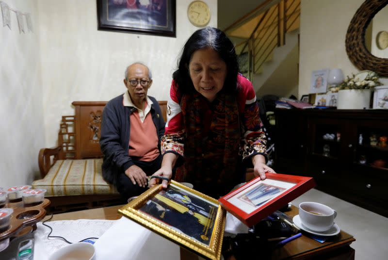 Nina Widyawati, 65-year-old mother of Ratih Purwarini, a doctor who passed away due to the coronavirus disease (COVID-19), shows photographs of her daughter, as her husband Bambang Purnomo Sidik sits at their house in Jakarta