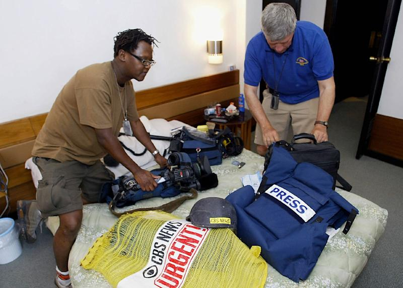 CBS news journalists prepare their equipment, including helmets and flack jackets, in Baghdad on April 13, 2004 (AFP Photo/Nicolas Asfouri)