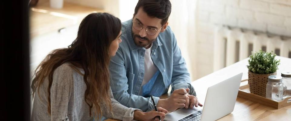 Couple at desk with laptop discussing money