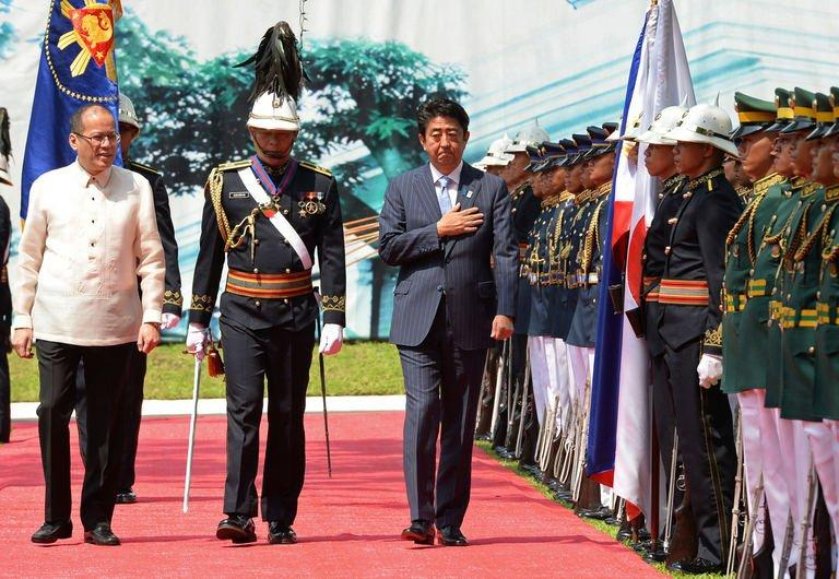 Japan's PM Shinzo Abe (R) and Philippine President Benigno Aquino (L) review an honour guard in Manila, on July 27, 2103