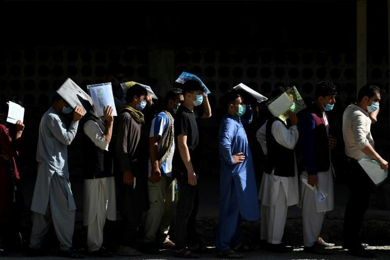 Afghan men line up to apply for a passport in Kabul, with a rush of applications ahead of the final withdrawal of foreign troops from the country