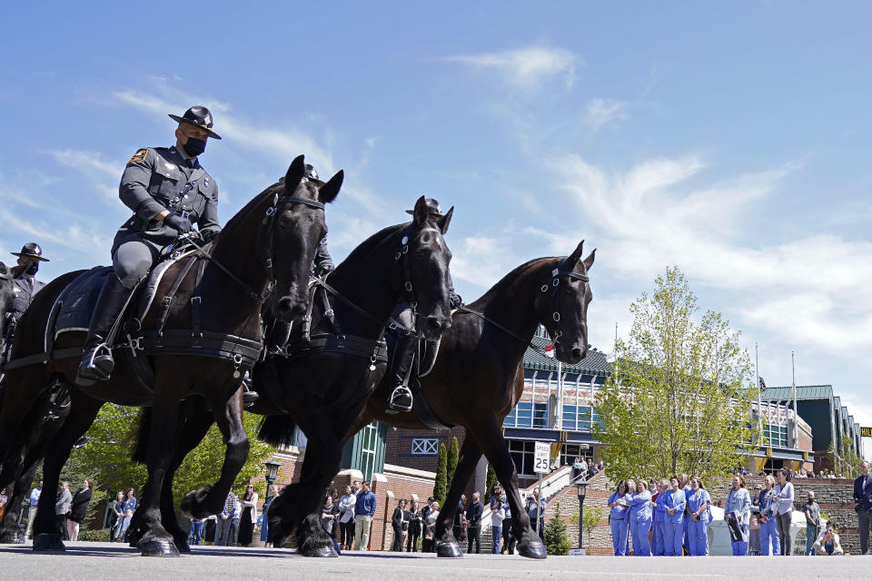 A processional passes the Holmes Convocational Center for the funeral services of Watauga County Sheriff's Deputies Sgt. Chris Ward and K-9 Deputy Logan Fox in Boone, N.C., Thursday, May 6, 2021. The two deputies were killed in the line of duty. (AP Photo/Gerry Broome)