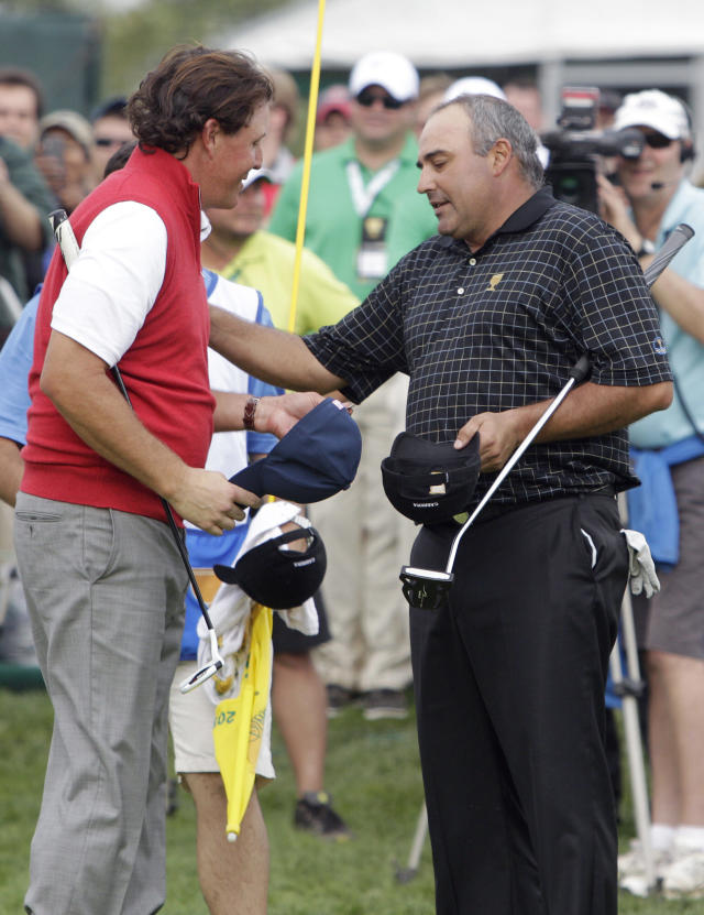 United States team player Phil Mickelson, left, meets with International team player Angel Cabrera, of Argentina, after the single matches at the Presidents Cup golf tournament at Muirfield Village Golf Club Sunday, Oct. 6, 2013, in Dublin, Ohio. (AP Photo/Jay LaPrete)