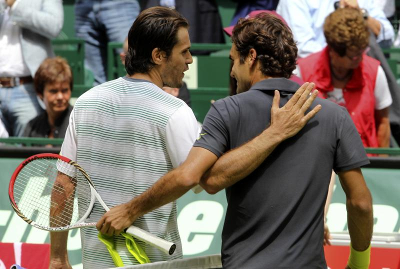 Germany's Tommy Haas , left, hugs Swiss Roger Federer after the final match of the Gerry Weber Open ATP tennis tournament in Halle, western Germany, Sunday June 17, 2012. Wild card Tommy Haas of Germany defeated five-time winner Roger Federer 7-6 (5), 6-4 to win the Gerry Weber Open for the second time on Sunday. The 87th-ranked Haas, the oldest player in the singles draw at 34, recovered from losing his serve in the first game by winning the first set on a tiebreaker and then getting the decisive break in the ninth game of the second set. (AP Photo/dapd/Joerg Sarbach)