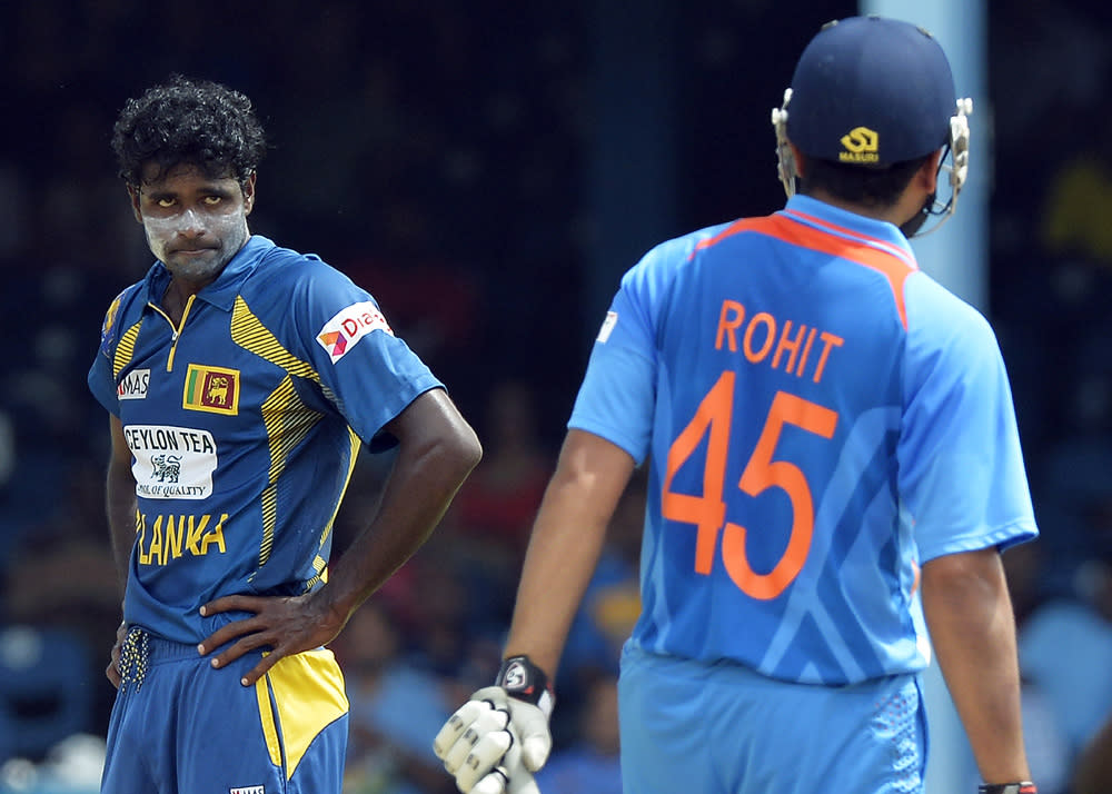 Sri Lankan cricketer Shaminda Eranga (L) reacts after a failed appeal against Indian batsman Rohit Sharma (R) during the final match of the Tri-Nation series between India and Sri Lanka at the Queen's Park Oval stadium in Port of Spain on July 11, 2013. Sri Lanka have scored 201/10. AFP PHOTO/Jewel Samad