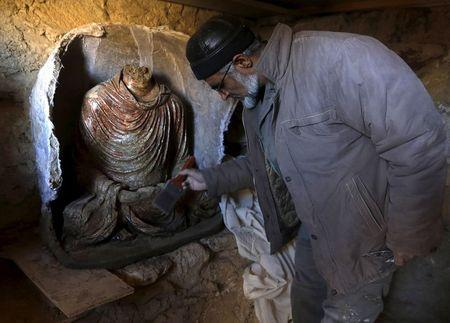 An Afghan archeologist cleans a  headless Buddha statue discovered inside an ancient temple in Mes Aynak, Logar province February 14, 2015.   REUTERS/Omar Sobhani