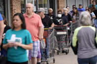 People wait for an H-E-B grocery store to open Tuesday, March 17, 2020, in Spring, Texas. Grocery store executives and city officials reassured the community that plenty of food will be available in their stores and urged people not to stockpile groceries amid coronavirus concerns. (AP Photo/David J. Phillip)