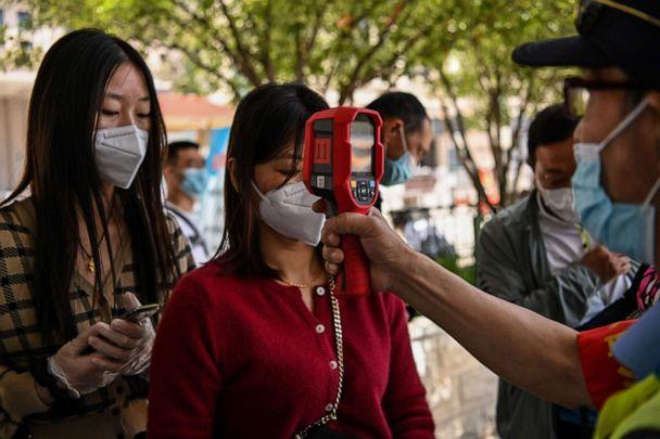 PHOTO: A worker wearing a face mask checks passengers' body temperatures as well as a health code on their cellphones before they take a taxi after arriving at Hankou railway station in Wuhan, in China's central Hubei province, on May 12, 2020. (Hector Retamal/AFP via Getty Images)