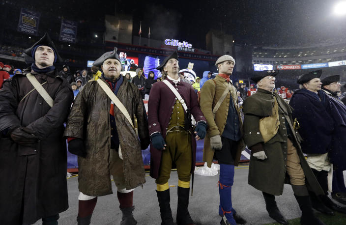 Patriot actors stand without their usual rifles to honor the victims of the Sandy Hook Elementary School shootings in Newtown, Conn., in the third quarter of an NFL football game between the New England Patriots and the San Francisco 49ers in Foxborough, Mass., Sunday, Dec. 16, 2012. (AP Photo/Elise Amendola)