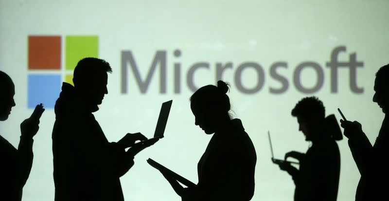 Silhouettes of laptop and mobile device users are seen next to a screen projection of Microsoft logo in this picture illustration