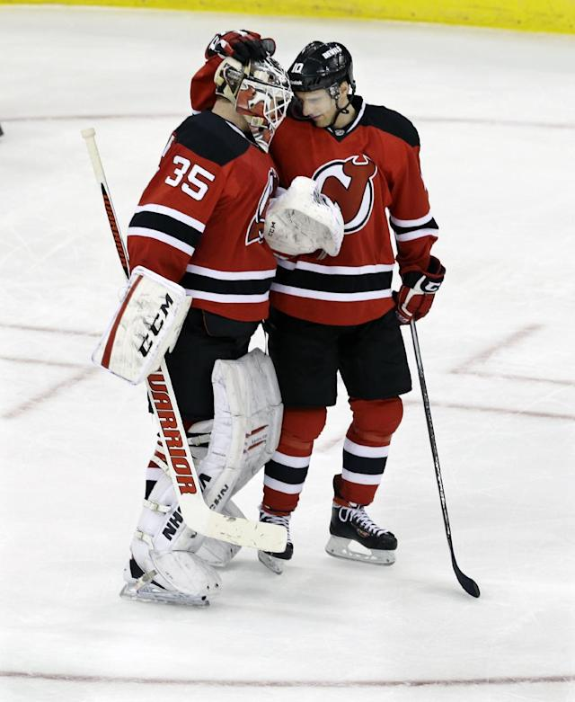 New Jersey Devils' Peter Harrold (10) congratulates goalie Cory Schneider (35) after defeating the Toronto Maple Leafs 3-2 in an NHL hockey game Sunday, March 23, 2014, in Newark, N.J. (AP Photo/Mel Evans)