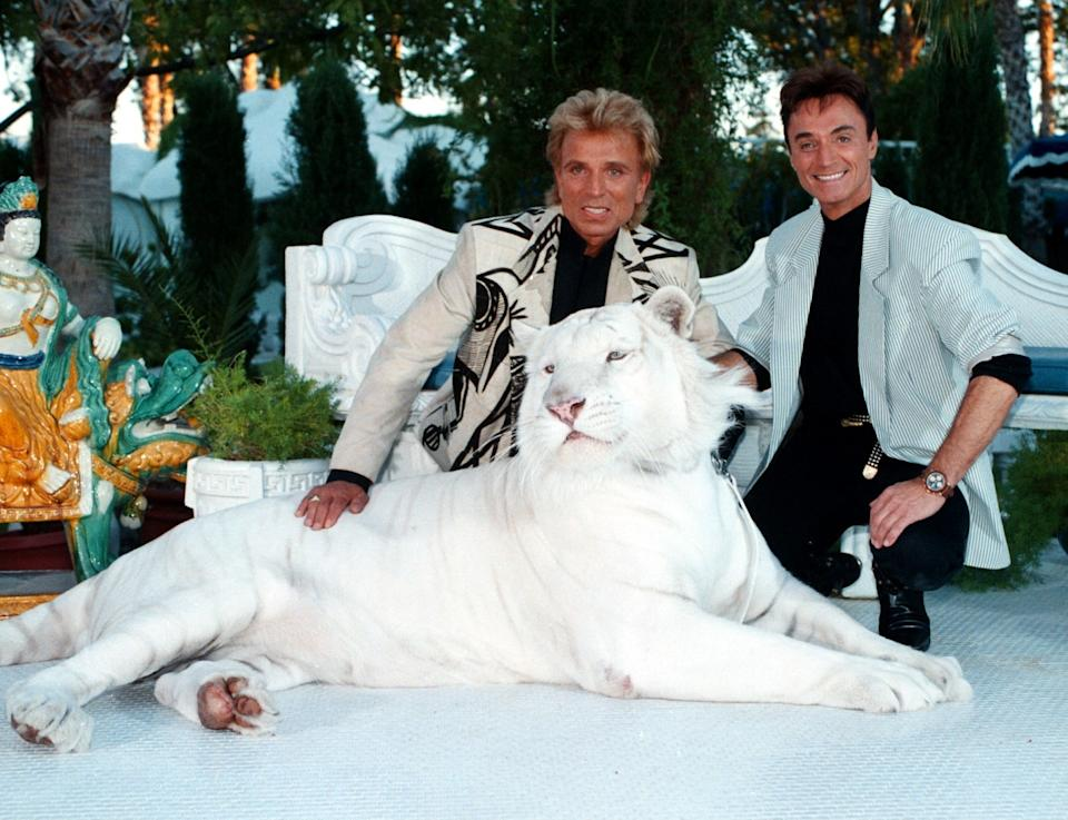 Siegfried & Roy pose with a white tiger. (Photo by Peter Bischoff/Getty Images)
