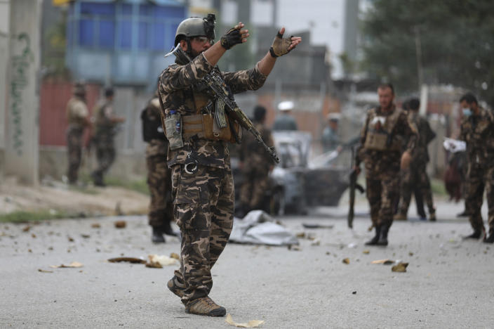 Security personnel inspect a damaged vehicle which was was firing rockets in Kabul, Afghanistan, Tuesday, July 20, 2021. At least three rockets hit near the presidential palace on Tuesday shortly before Afghan President Ashraf Ghani was to give an address to mark the Muslim holiday of Eid-a-Adha. (AP Photo/Rahmat Gul)