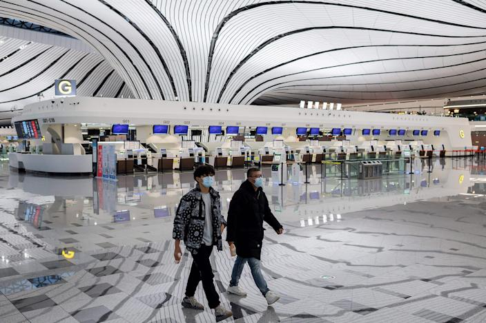 This picture taken on February 14, 2020 shows two men wearing face masks walking through a nearly empty terminal at Daxing international airport in Beijing, as travel has ground to a halt in the wake of the the COVID 19 coronavirus outbreak. 2
