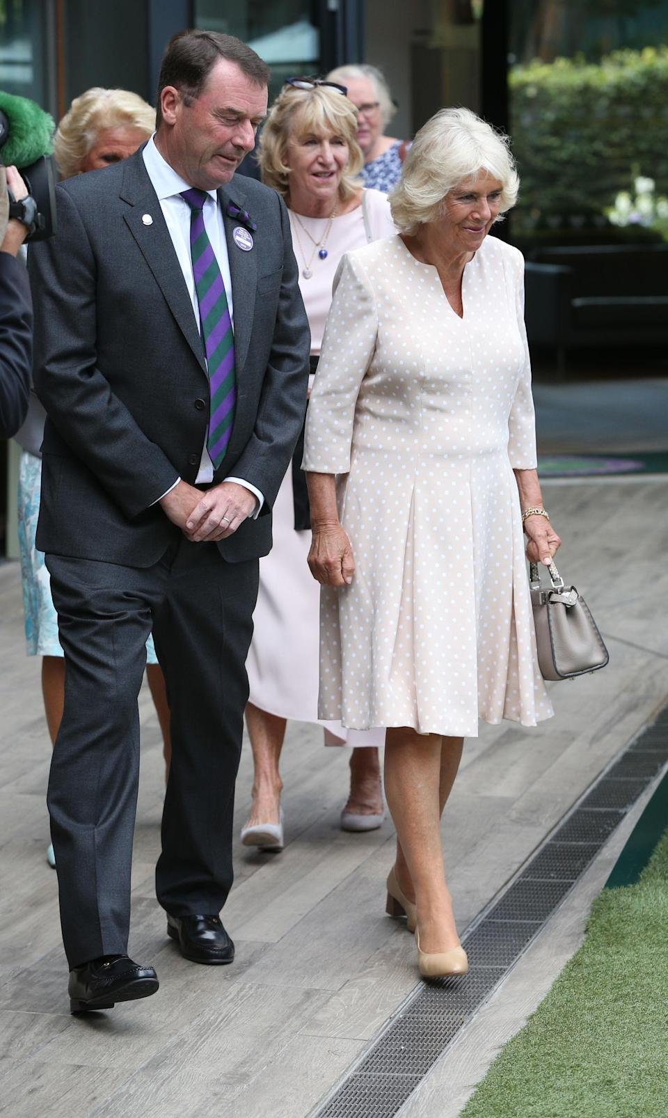 <p>The Duchess of Cornwall donned this season's most coveted look at Wimbledon 2018, polka dots. She teamed the v-neck dress with a miniature handbag and sand-hued shoes. <em>[Photo: PA]</em> </p>
