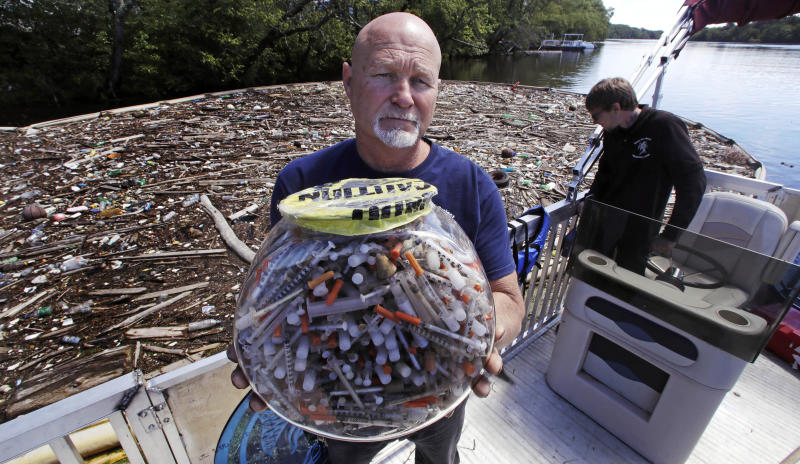 """In this Wednesday June 7, 2017 photo, activist Rocky Morrison, of the """"Clean River Project"""", holds up a fish bowl filled with hypodermic needles, that were recovered during 2016, on the Merrimack River next to their facility in Methuen, Mass. Morrison leads a cleanup effort along the Merrimack River, which winds through the old milling city of Lowell, and has recovered hundreds of needles in abandoned homeless camps that dot the banks, as well as in piles of debris that collect in floating booms he recently started setting. (AP Photo/Charles Krupa)"""