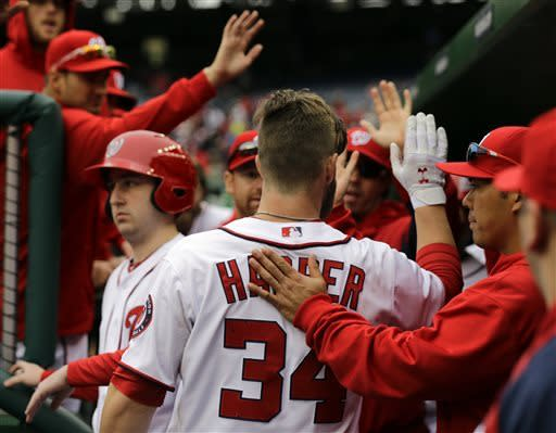 Washington Nationals left fielder Bryce Harper (34) celebrates teammates after scoring during the first inning of a baseball game against the Miami Marlins at Nationals Park, Thursday, April 4, 2013, in Washington. (AP Photo/Alex Brandon)