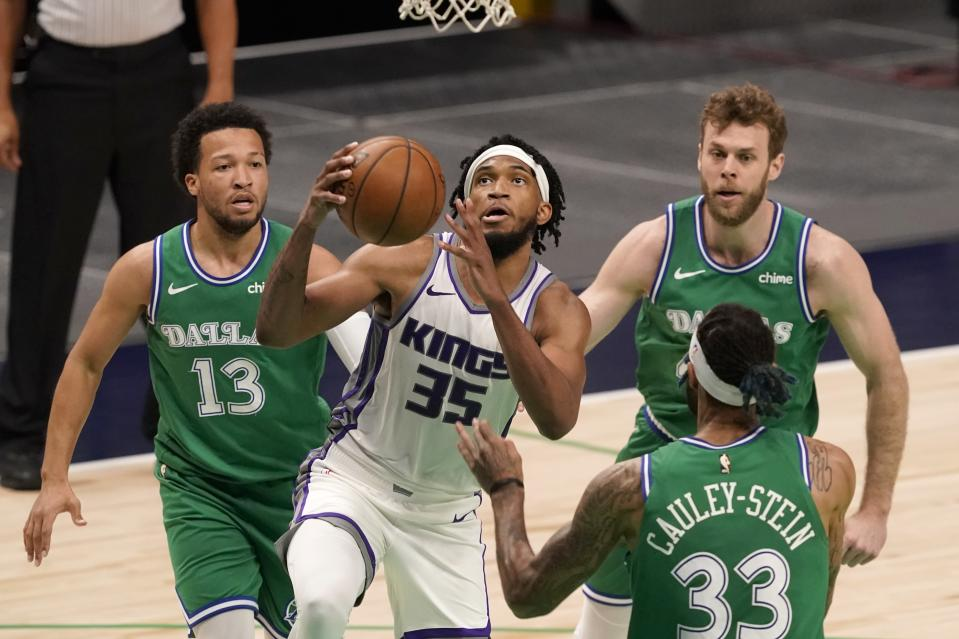 Sacramento Kings forward Marvin Bagley III (35) goes up for a shot between Dallas Mavericks' Jalen Brunson (13), Willie Cauley-Stein (33) and Nicolo Melli, right rear, in the second half of an NBA basketball game in Dallas, Sunday, May 2, 2021. (AP Photo/Tony Gutierrez)