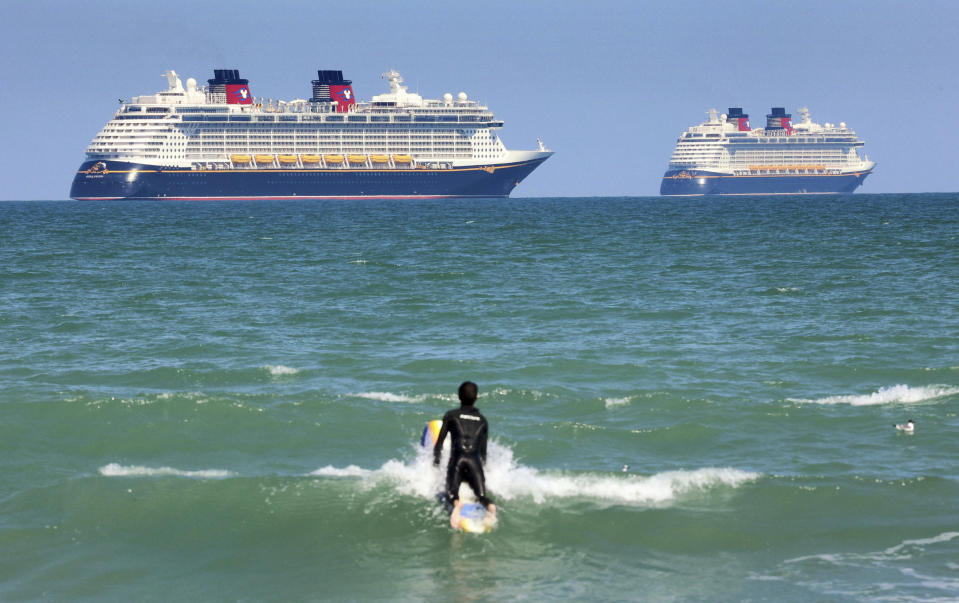 "FILE - In this March 24, 2021 file photo, a surfer eyes the Disney Cruise Line ships ""Fantasy, "" left, and ""Dream"" on the horizon as they sit stationary off of Cocoa Beach, Fla., in this view from Lori Wilson Park. Florida is threatening to sue the federal government if it doesn't lift its pandemic ban on cruise lines using U.S. ports. Gov. Ron DeSantis and state Attorney General Ashley Moody said Friday, March 26, that the state is being harmed economically by the industry's U.S. shutdown. (Joe Burbank/Orlando Sentinel via AP, File)"