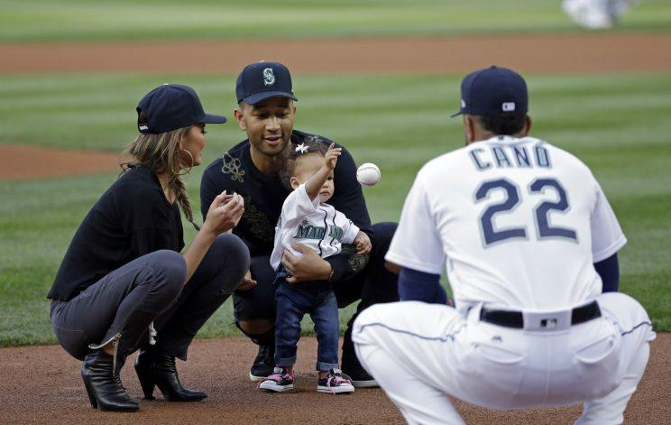 Entertainer John Legend, center, and his wife Chrissy Teigen help their daughter Luna Stephens throw out the ceremonial first pitch to Seattle Mariners' Robinson Cano before a baseball game against the Minnesota Twins Tuesday, June 6, 2017, in Seattle. (AP Photo/Elaine Thompson)
