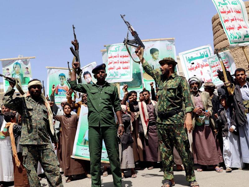 Houthi soldiers protest an offer by the Saudi-led coalition to pay compensation for victims of an airstrike in Saada, Yemen (Reuters)
