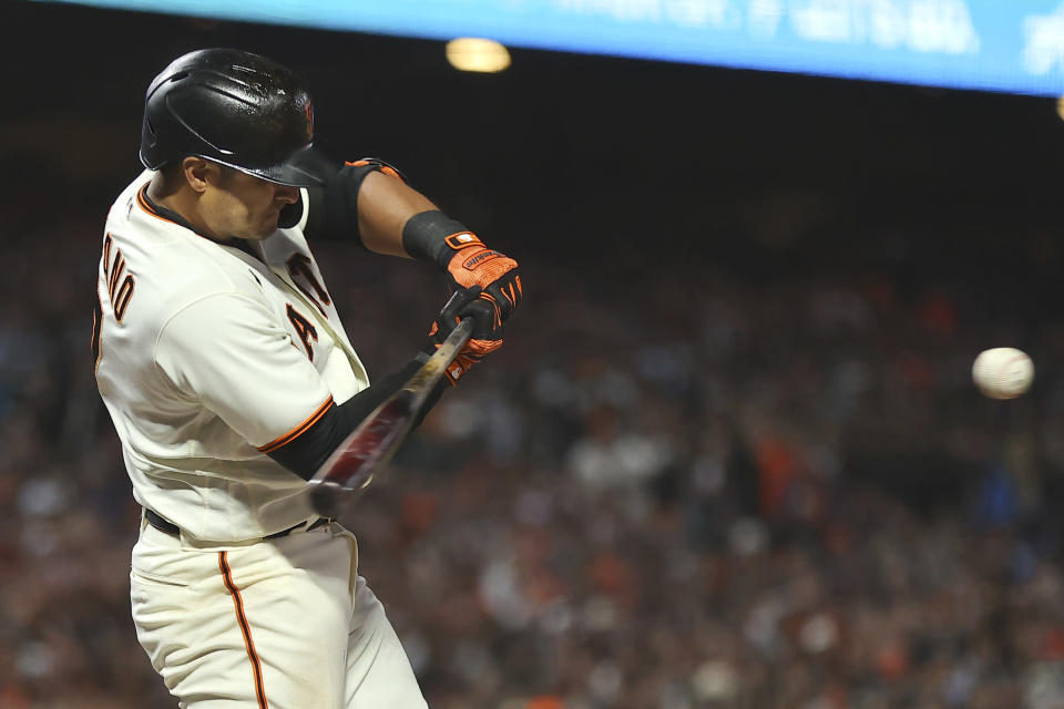 San Francisco Giants' Donovan Solano hits a sacrifice fly to score Wilmer Flores during the second inning of Game 2 of a baseball National League Division Series against the Los Angeles Dodgers Saturday, Oct. 9, 2021, in San Francisco. (AP Photo/John Hefti)