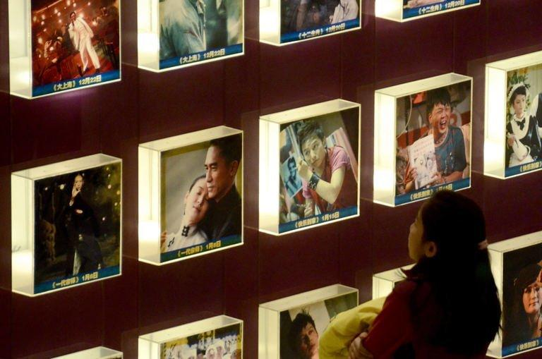 A woman looks at a set of illuminated movie posters at a cinema in Beijing on January 18,2013