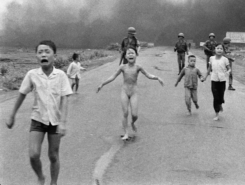 FILE - In this June 8, 1972 file photo, crying children, including 9-year-old Kim Phuc, center, run down Route 1 near Trang Bang, Vietnam after an aerial napalm attack on suspected Viet Cong hiding places as South Vietnamese forces from the 25th Division walk behind them. A South Vietnamese plane accidentally dropped its flaming napalm on South Vietnamese troops and civilians. From left, the children are Phan Thanh Tam, younger brother of Kim Phuc, who lost an eye, Phan Thanh Phouc, youngest brother of Kim Phuc, Kim Phuc, and Kim's cousins Ho Van Bon, and Ho Thi Ting. (AP Photo/Nick Ut)