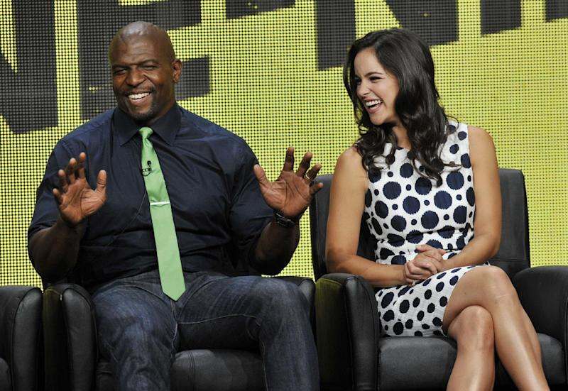"FILE - In this Aug. 1, 2013 photo, Terry Crews, left, and Melissa Fumero, cast members in the FOX series ""Brooklyn Nine-Nine,"" share a laugh onstage during the FOX 2013 Summer TCA press tour at the Beverly Hilton Hotel, in Beverly Hills, Calif. Fox says the plum post-Super Bowl slot next February will be filled by two of its comedies. ""New Girl"" and freshman series ""Brooklyn Nine-Nine"" will air on Fox after the game that's typically TV's most-watched program and a big promotional platform for other network fare. (Photo by Chris Pizzello/Invision/AP, File)"