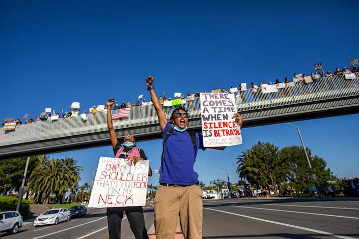 Image: Protesters hold signs during a demonstration over the death of George Floyd in Newport Beach, Calif., on June 3, 2020. (Apu Gomes / AFP - Getty Images file)