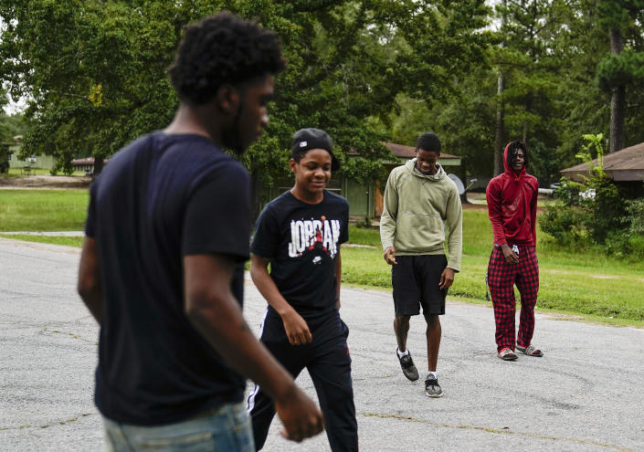 Voen Ivey, 18, left, JJ Ivey, 13, right center, Jay Johnson, 19, center, and Te Moss, 18, right, gather in front of their neighborhood in Hancock County, Saturday, Sept. 19, 2020, in Mayfield, Ga. Early on, victims of the coronavirus were mostly residents of the county's two nursing homes. Now, it's younger residents too. Coroner Adrick Ingram sees young people in town not wearing masks and gathering in big groups, and it frustrates him. ''I see people who aren't taking it seriously, maybe because they don't see what I see. They don't get to look in people's faces when they've lost somebody.'' (AP Photo/Brynn Anderson) (AP Photo/Brynn Anderson)