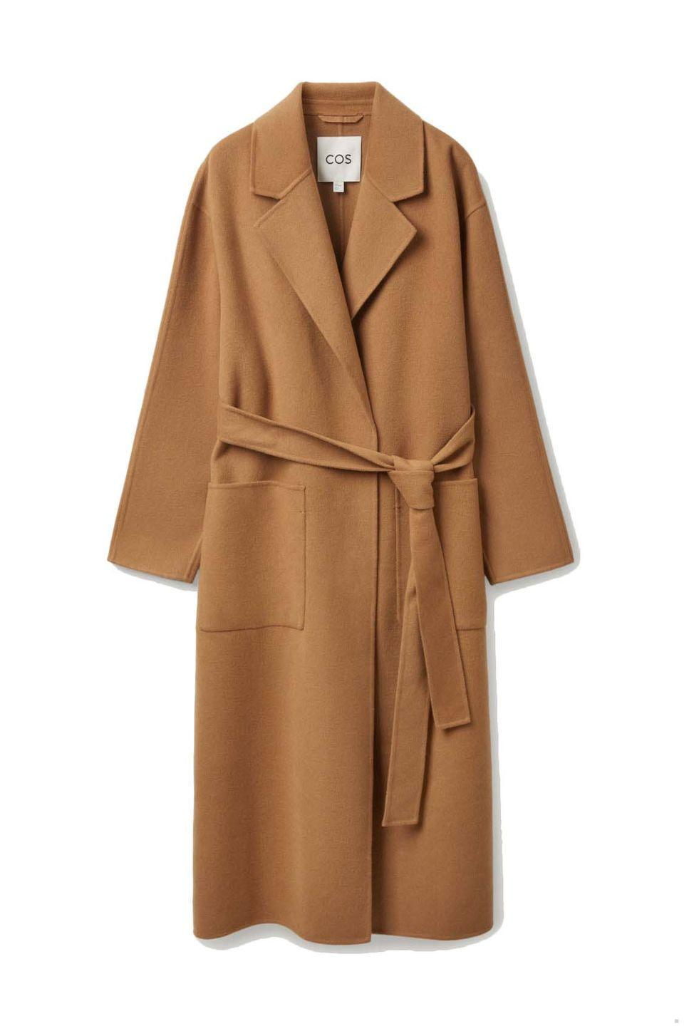 """<p><a class=""""link rapid-noclick-resp"""" href=""""https://www.cosstores.com/en_gbp/women/womenswear/coats-and-jackets/coats/product.belted-wrap-coat-beige.0996812003.html"""" rel=""""nofollow noopener"""" target=""""_blank"""" data-ylk=""""slk:SHOP NOW"""">SHOP NOW</a></p><p>Cos' camel coat is made from responsibly-sourced wool and Tencel™ lyocell fibres (derived from wood pulp), so it's a more sustainable choice. We like how this classic wrap style is left unlined, to allow for easy layering in the trans-seasonal months.</p><p>Belted Wrap Coat, £190, Cos</p>"""