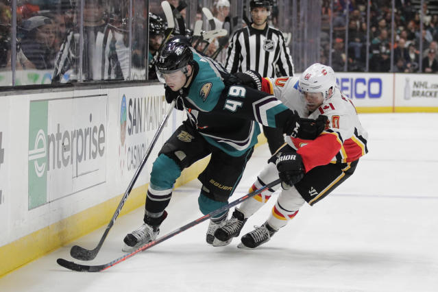 Anaheim Ducks' Max Jones, left, moves the puck past Calgary Flames' Derek Ryan during the second period of an NHL hockey game Wednesday, April 3, 2019, in Anaheim, Calif. (AP Photo/Jae C. Hong)