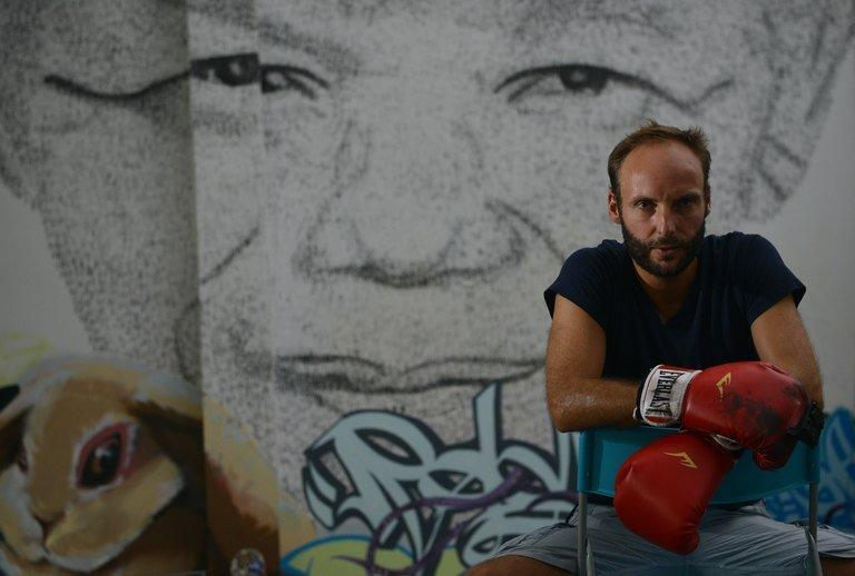 """Shanghai-based 34 year-old Belgian artist Phil Akashi poses in front of his portrait of South African peace icon and former boxer Nelson Mandela, which he forged by pounding the wall 27,000 times with a boxing glove bearing Chinese character for """"freedom"""", on August 1, 2013"""