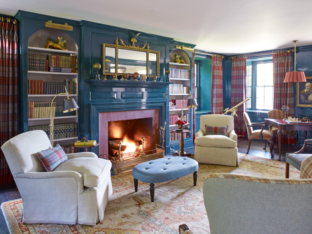 "<p>Designer <a href=""https://www.richardkeithlangham.com/"">Richard Keith Langham</a> transforms the former living room of this 1850s Pennsylvania farmhouse into a high-style library. A <a href=""http://www.cowtan.com/"">Colefax and Fowler</a> plaid evokes the homeowner's Scottish heritage and playfully reflects off of blue-violet lacquered walls. The library's club chairs are in a linen chenille, and the custom ottoman is in a <a href=""https://www.jerrypair.com/"">Jerry Pair</a> suede.</p>"