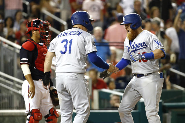 Los Angeles Dodgers' Justin Turner, right, celebrates with teammate Joc Pederson in front of Washington Nationals catcher Kurt Suzuki, back left, after batting in Pederson on a three-run home run in the eighth inning of a baseball game, Friday, July 26, 2019, in Washington. (AP Photo/Patrick Semansky)