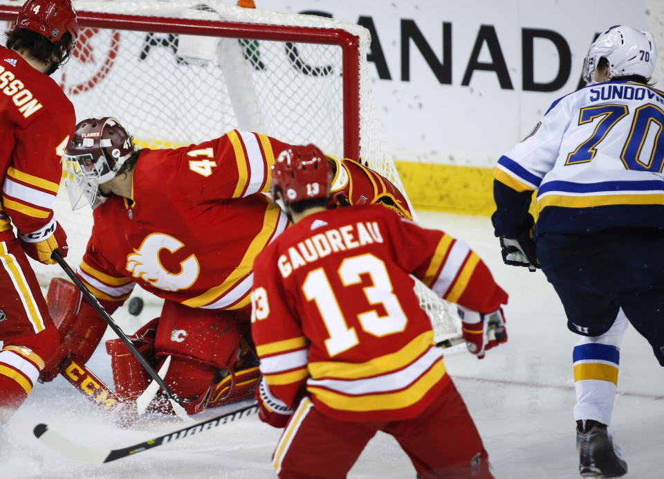 St. Louis Blues' Oskar Sundqvist, right, of Sweden, scores against Calgary Flames goalie Mike Smith during third-period NHL hockey game action in Calgary, Alberta, Saturday, Dec. 22, 2018. (Jeff McIntosh/The Canadian Press via AP)