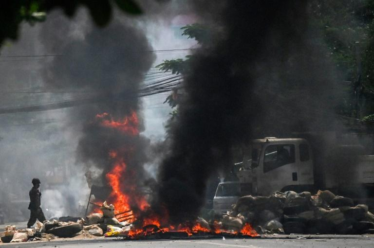 Soldiers set fire to barricades erected by protesters in Yangon