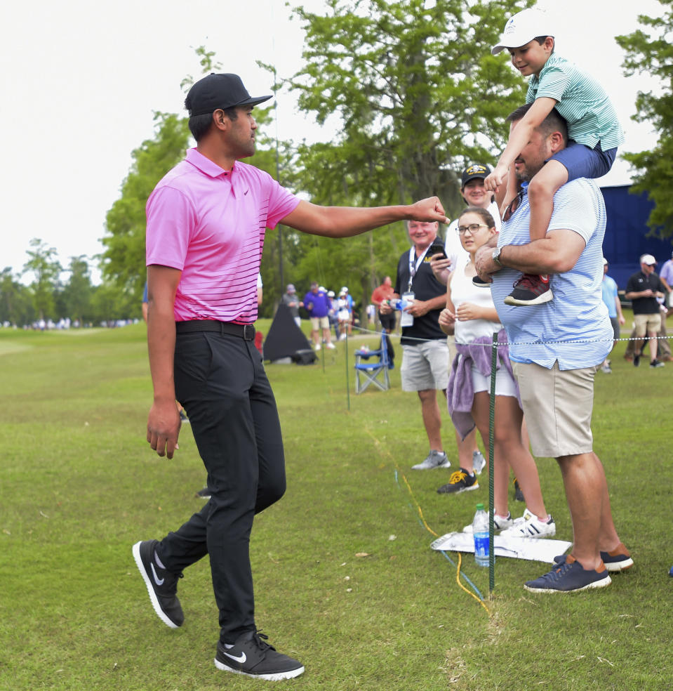 Tony Finau bumps fists with a young fan during the second round of the Zurich Classic golf tournament at TPC Louisiana in Avondale, La., Friday, April 23, 2021. (Max Becherer/The Times-Picayune/The New Orleans Advocate via AP)